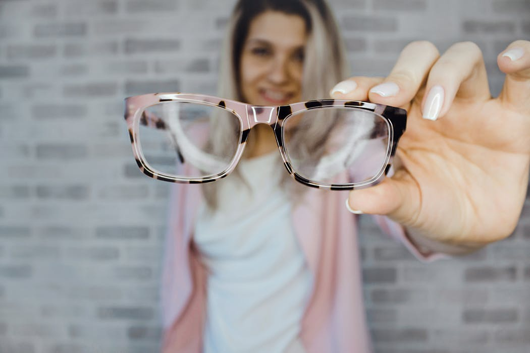 woman holding a stylish eye glasses