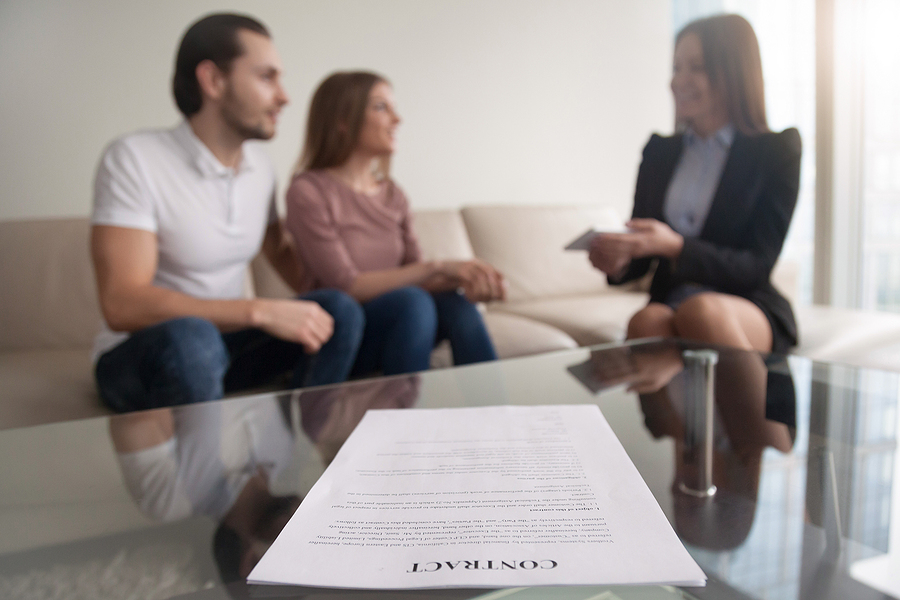 Young couple and a lawyer discussing prenuptial agreement