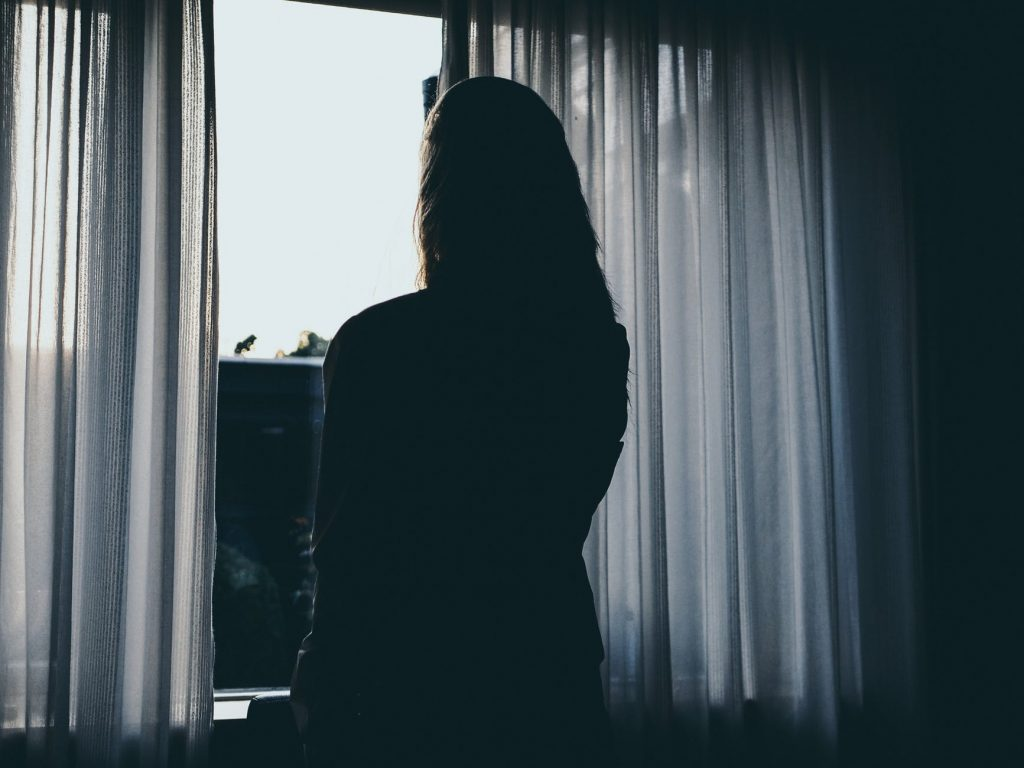 Woman looking over blockout curtains in the window